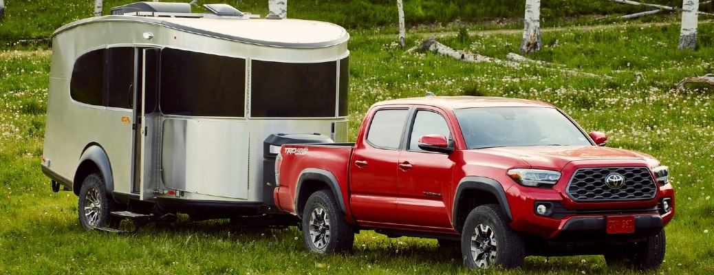 The front and side view of a red 2021 Toyota Tacoma hauling an Airstream travel trailer.