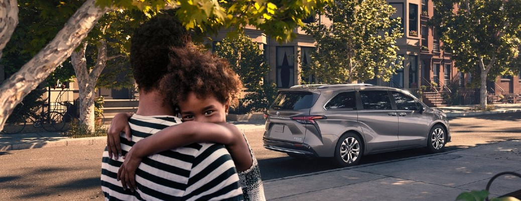 A young girl being carried towards a gray 2021 Toyota Sienna.