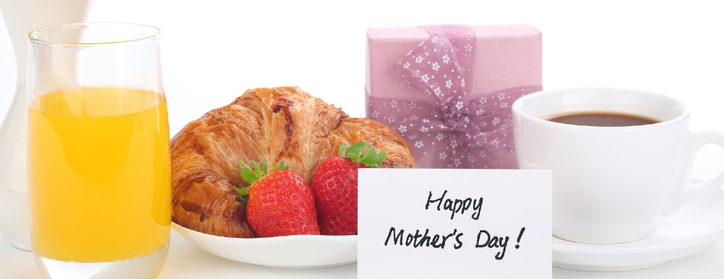 """An assortment of juice, coffee, and breakfast foods with a note that says """"Happy Mother's Day!""""."""