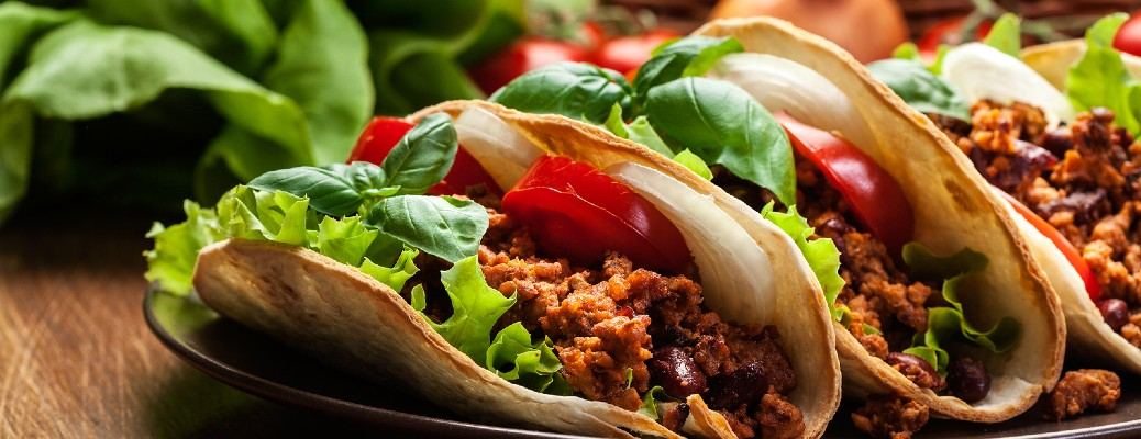 Three beef tacos filled with cheese and vegetables on a plate.