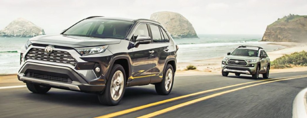 The front and side view of two gray 2021 Toyota RAV4 models driving on a road.