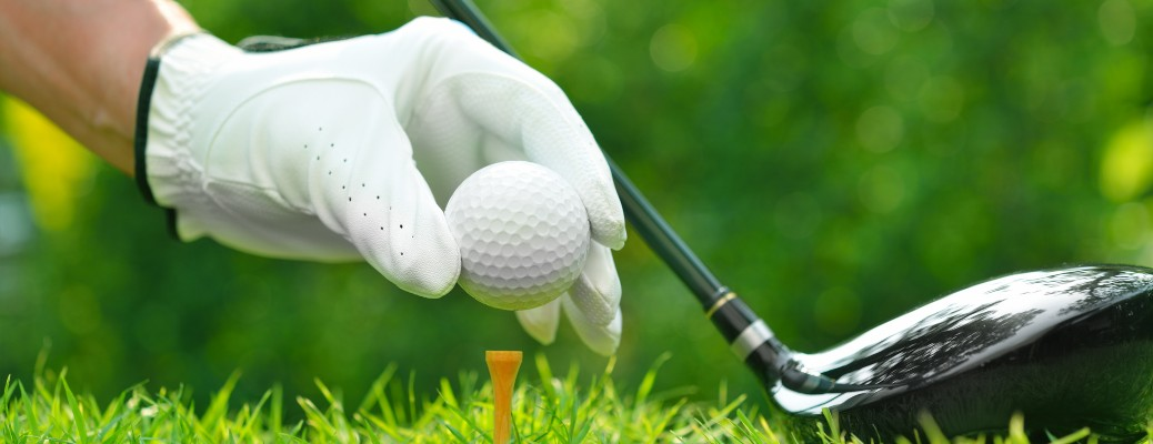 A man holding a golf ball ready to tee off.
