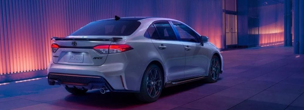 Rear side view of a grey 2022 Toyota Corolla Apex Edition driving on a road at night