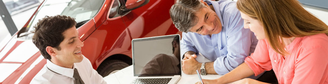 HAppy couple signing paperwork at dealership