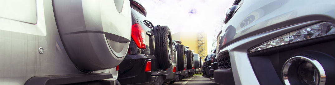 Rear exteriors of a line of SUVs at the car lot