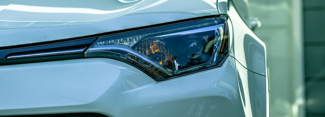 close up of white cars driver side-headlight
