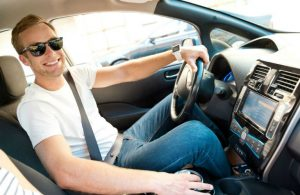 smiling man switching gears in vehicle