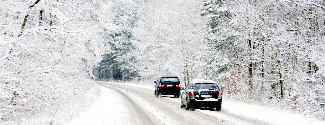 two cars driving on a snow covered road with snow covered trees lining the road