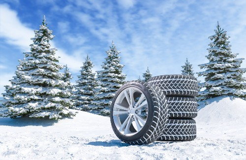 stack of winter tires in a snow covered pine tree forest