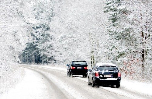 two cars driving on a snow covered road