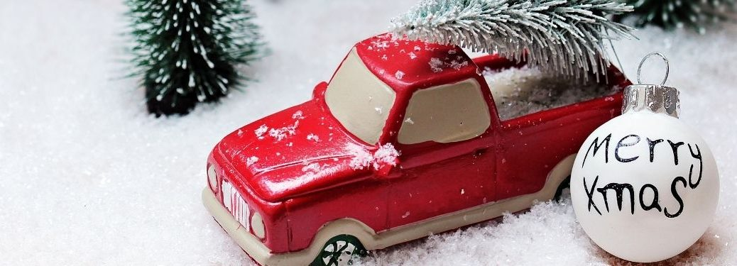 toy truck with fake tree on top fake snow and merry xmas ornamen
