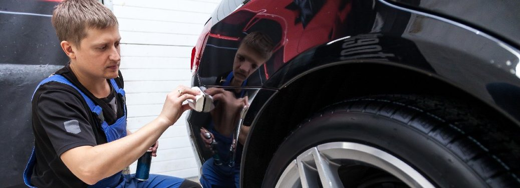 man buffing out paint on car