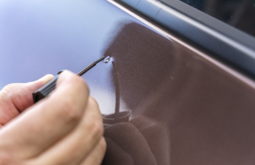person using small brush to paint chipped paint on car