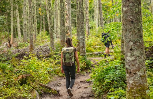 man and woman hiking in woods with backpacks