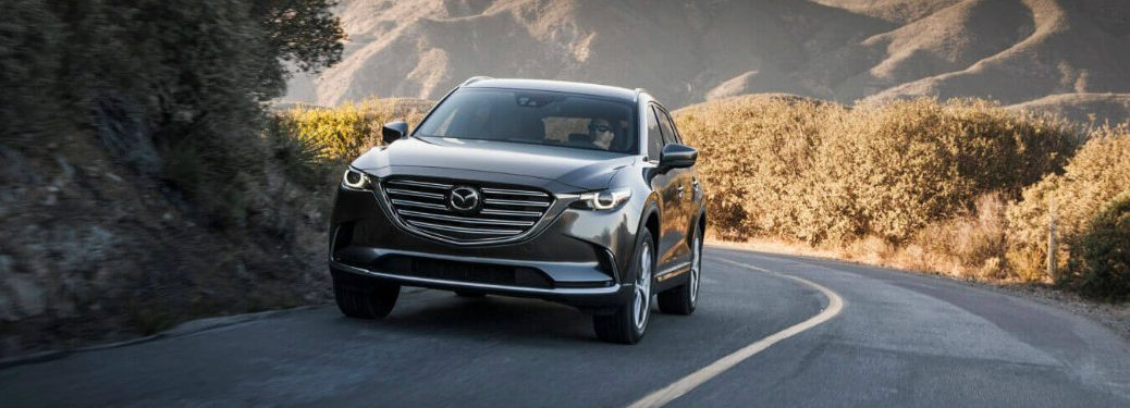 gray mazda cx-9 driving on hilly road