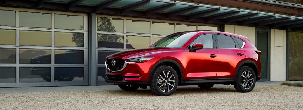 left side of red mazda cx-5 parked in front of garage