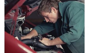 Mechanic looking into a car engine