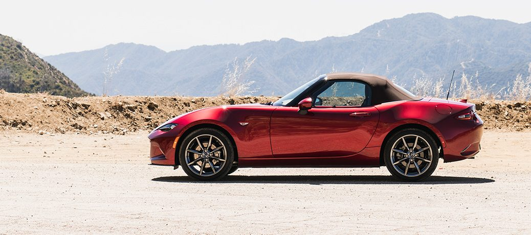 red mazda mx-5 parked in sand in front of mountain