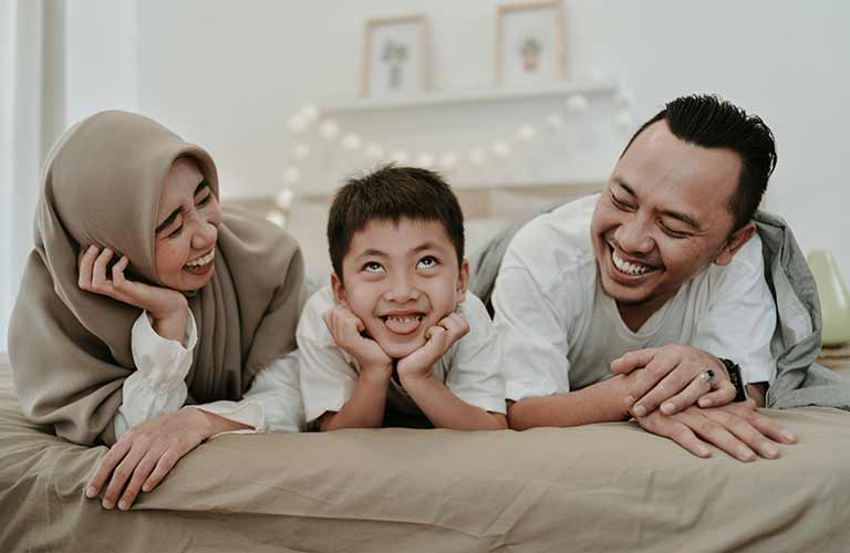 parents and kid on a bed