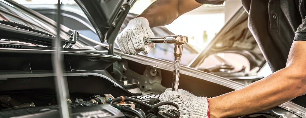 person working under hood of vehicle