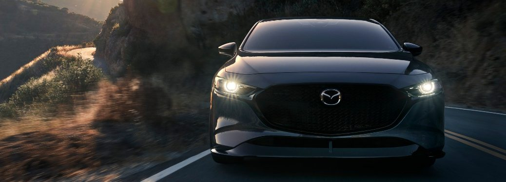 2021 Mazda3 Sedan driving down a rural road