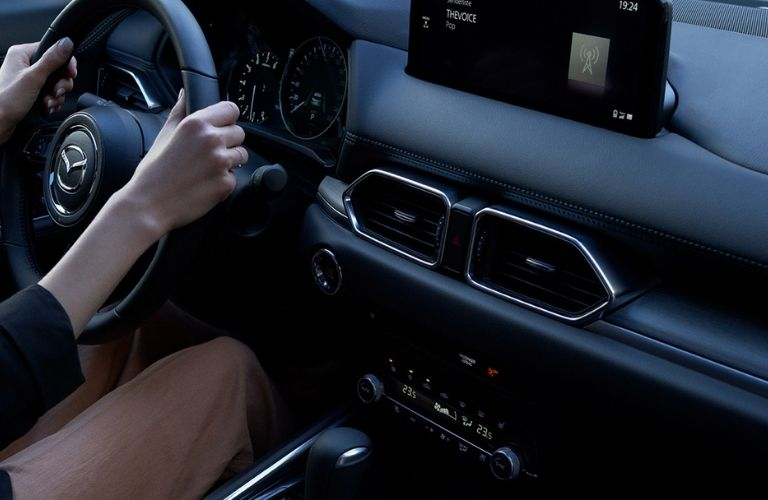 front interior view of the 2022 mazda cx-5 with driver's hands on the steering wheel