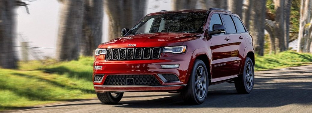 Front driver angle of a red 2020 Jeep Grand Cherokee driving down a road