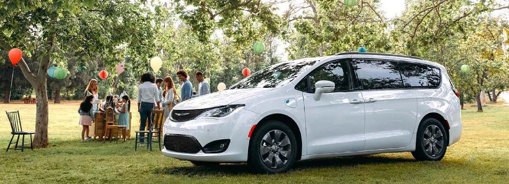 Front driver angle of a white 2020 Chrysler Pacifica parked near a birthday party in the park