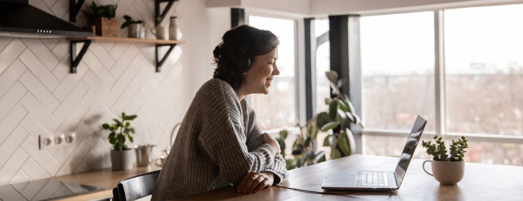woman smiling and chatting on laptop in kitchen