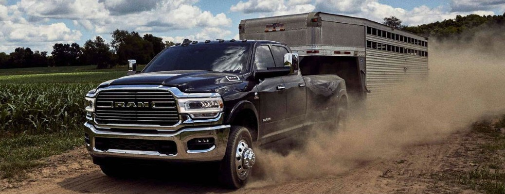 2020 Ram 3500 black exterior front driver side driving on dirt road in corn field towing horse trailer