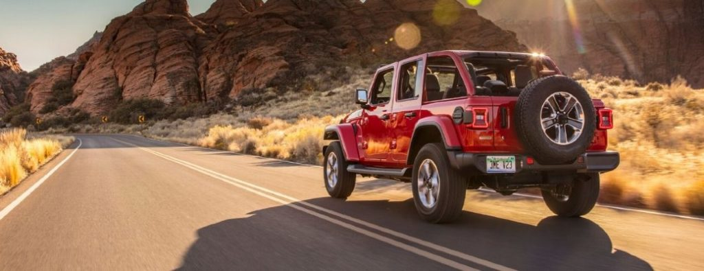 2020 Jeep Wrangler red exterior rear driver side driving in desert