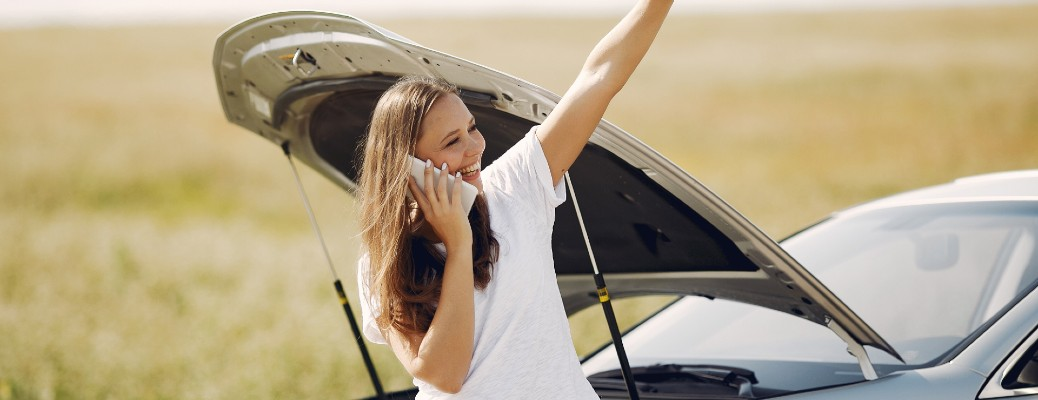girl in front of broken down car on phone holding up hand