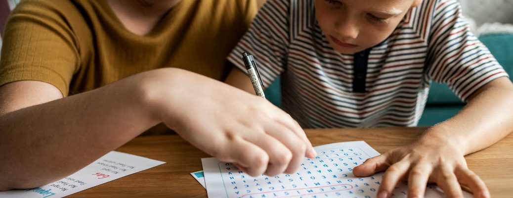 Two people playing a word search game on paper