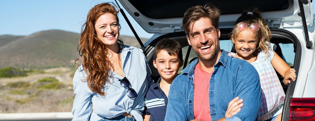 Family sitting in the cargo area of a vehicle while out on the road