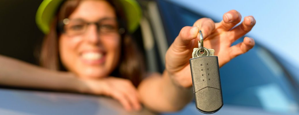 Young woman with keys to a car