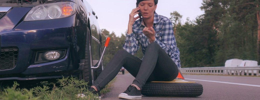 Woman on phone sitting on flat tire
