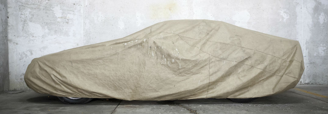 Car covered in gray sheet