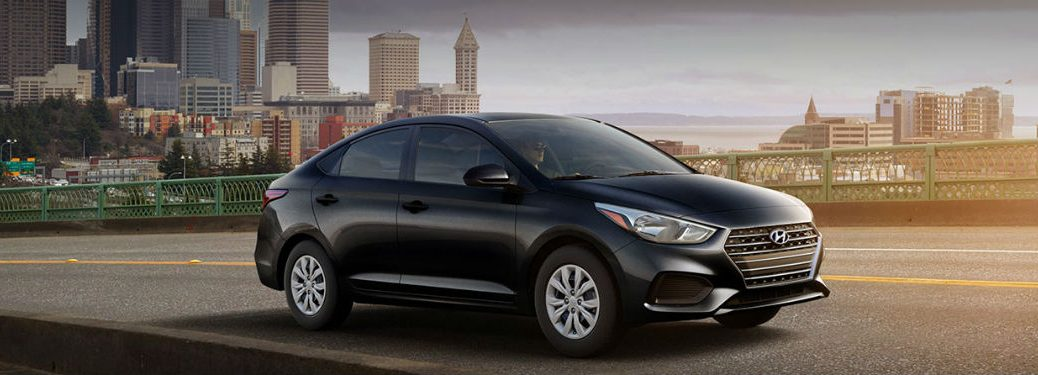 2020 Hyundai Accent black exterior passenger side front fascia driving with city background