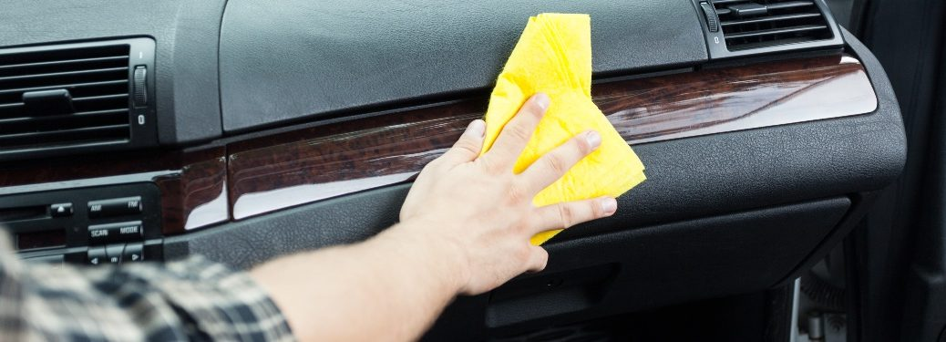 Person cleaning the dashboard of a vehicle