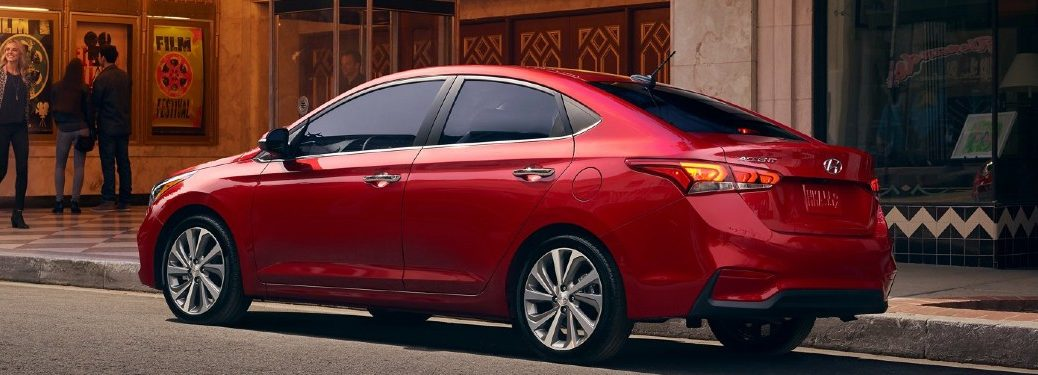 2021 Hyundai Accent red exterior rear fascia passenger side parked outside of movie theater