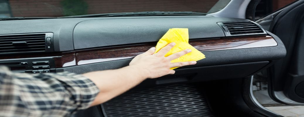 Detailing cloth wiping down a dashboard