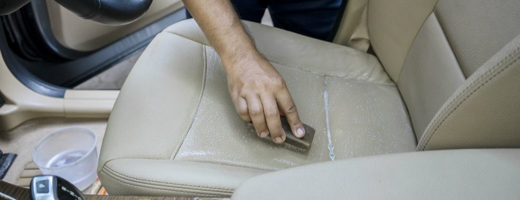 Leather seat being brushed and cleaned