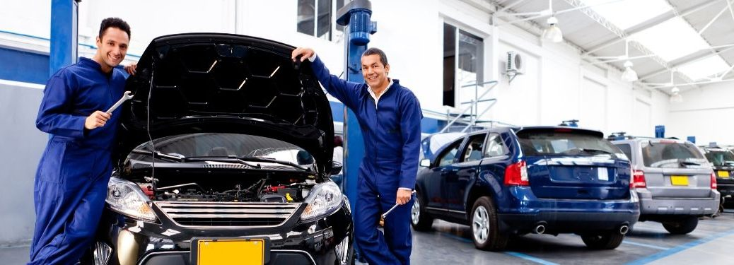 Two mechanics standing next to car smiling