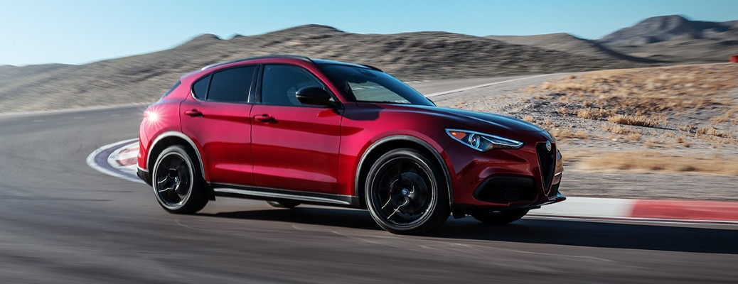 The side view of a red 2020 Alfa Romeo Stelvio on a race track.