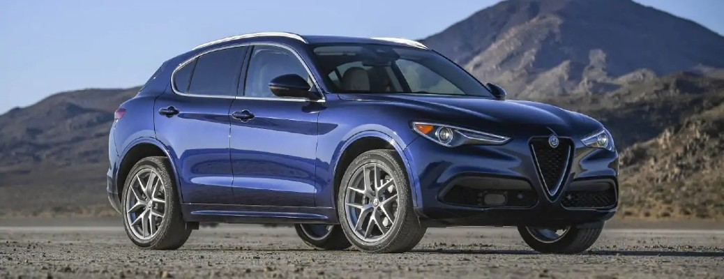 The front and side image of a purple 2021 Alfa Romeo Stelvio parked in front of a mountain.
