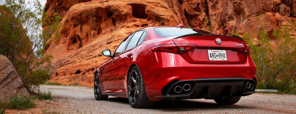 The rear and side view of a red 2021 Alfa Romeo Giulia Quadrifoglio parked in front of a red rock face.