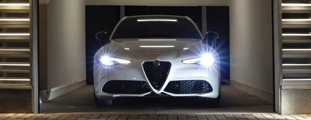 The front side of a white 2021 Alfa Romeo Giulia with its lights on.