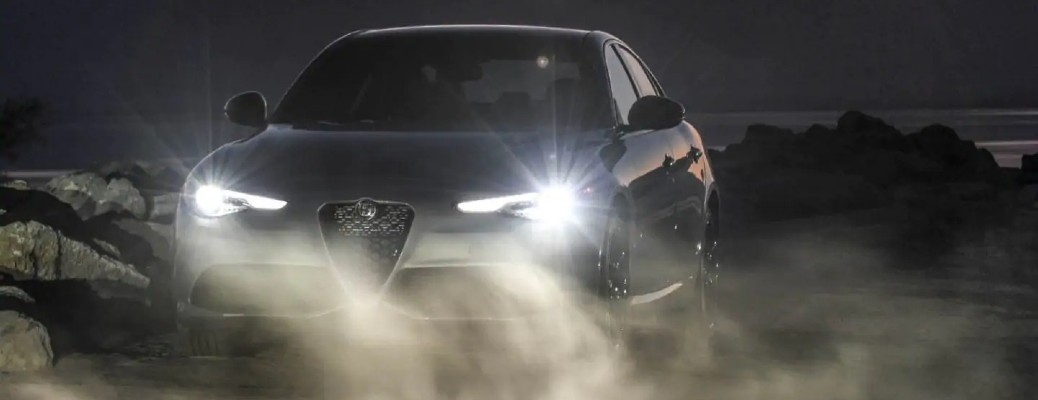 The front side of a 2021 Alfa Romeo Giulia with its lights on in the fog.