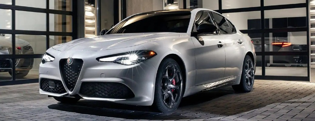 The front and side view of a white 2021 Alfa Romeo Giulia parked in a garage.