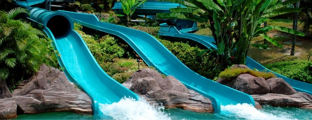 water slides in a water park with greenery around